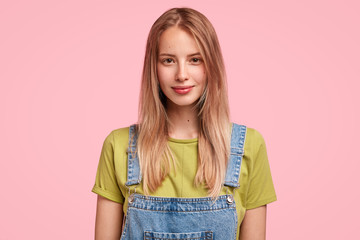 Wall Mural - Candid shot of good looking Caucasian female with long straight hair, wears jean dungaree, looks confidently at camera, enjoys spare time, going to have walk with her dog outside. Beauty concept