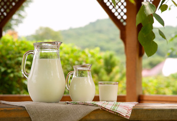 A lot of milk on the windowsill of the pergola. Two jugs of milk and a glass on the windowsill of a wooden pergola. Milk on a background of green leaves and tree branches.