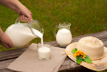Milk is poured into a glass. Female hands hold a jug of milk. Milk is poured into a glass on a wooden bench. Green grass, a bench and a straw hat remind of a village.