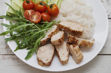 White plate with baked chicken breast, whited steamed rice, green arugula leaves (rocket salad), cucumber slices and red cherry tomatoes. Healthy eating concept