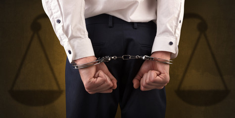 Arrested businessman in handcuffs with hands behind back and justice symbol wallpaper