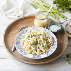 Fresh homemade pasta with asparagus, cheese and cream sauce on wooden tray.