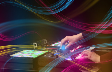 Hand mixing music on midi controller with colorful vibe concept