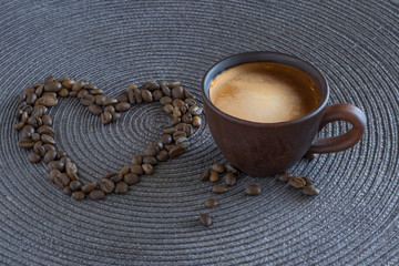 Cup of coffee and coffee beans in the form of heart on a dark gray background.