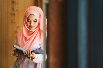 Beautiful Muslim girl reading book with hijab