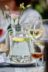 Table laying concept. On the table stands a jug with water and lemon. Glasses in the background.