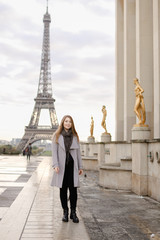 Young girl in grey coat standing on Trocadero square near gilded statues and Eiffel Tower in Paris. Concept of trip to France and European landmarks.