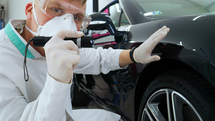 Professional master after polishing and painting cars, checks the flashlight scratches, a respirator, white rubber gloves, white coat, goggles, auto service.