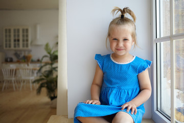 Indoor shot of beautiful little girl of preschool age sitting on windowsill with funny ponytail, dressed in blue dress, smiling happily at camera, having carefree look, modern kitchen in background