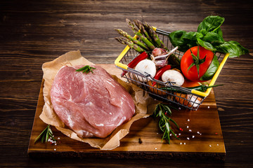 Fresh raw pork on cutting board on wooden background