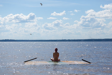 A girl in the summer meditates on a platform covered with water, installed in water near the shore of the Gorky reservoir, which is part of the Volga River