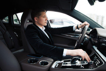 Do not hurry up! Handsome smart serious entrepreneur sitting on the driver's seat and carefully driving the automobile.