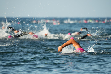 Group people in wetsuit swimming at triathlon