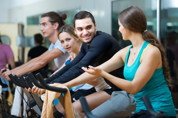 Young adults on exercise bikes in gym.