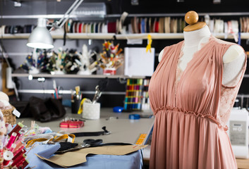 Workplace  with mannequin with dress in sewing shop of clothes factory