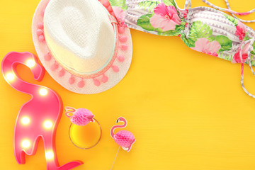 Top view of fashion female swimsuit bikini and white fedora hat on yellow wooden background. Summer beach vacation concept.