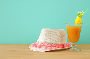image of tropical and exotic fruit coctail next to white fedora hat over wooden table.