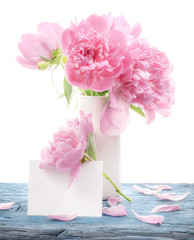 Bouquet of peonies flowers in white vase with paper blank isolated on white