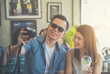 Young asian couple taking their photo by camera in coffee shop