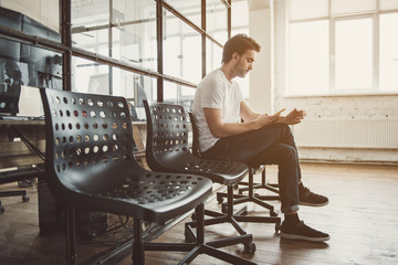 Full length side view serene man typing in mobile while resting on chair inside