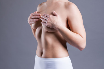 Woman examining her breasts for cancer, pain on female body
