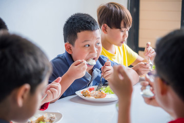 Young asian boy having lunch with friends at school canteen
