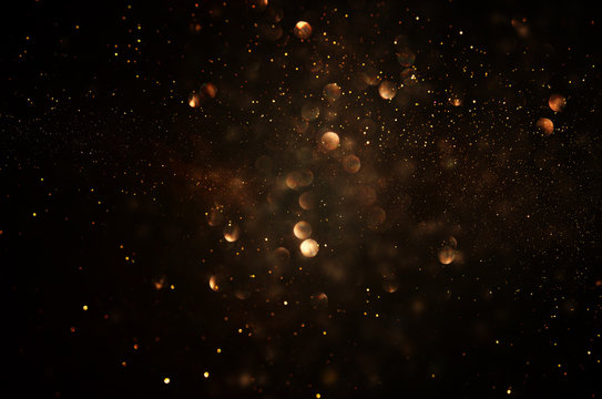 glitter vintage lights background. dark gold and black. de focused.
