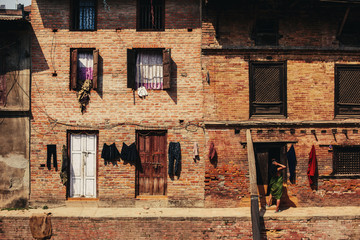 Traditional old brick building life in city Bhaktapur, Nepal. Opened windows, drying clothes, ancient shutters