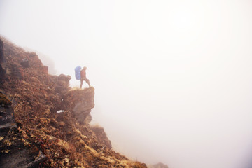 Female traveller with big backpack staying on the top of mountain cliff in white fog above clouds and valley, enjoy view