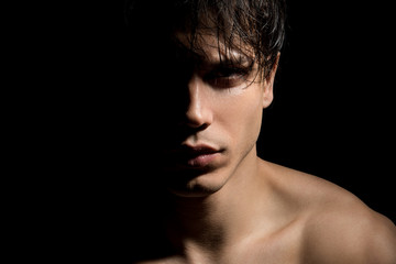 Close up portrait of young mysterious guy with half face in shadow. He is standing on dark background and expressing thoughtfulness. Masculine beauty concept