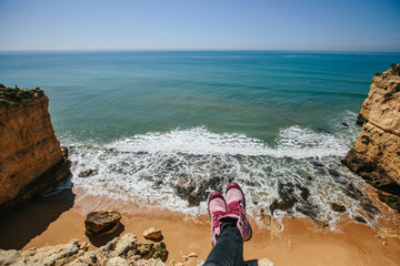Legs wearing pink sneakers with ocean cliff view background