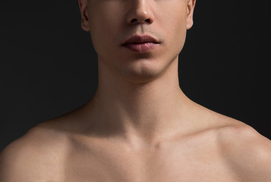 Close up of young male neck and half of face. Topless guy is demonstrating perfect healthy soft skin. Dark wall in background. Skincare concept