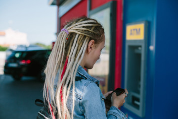 Young woman using mobile bank to remove limits and get money from atm