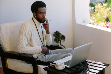 Portrait of man, smoking and using laptop at home. Freelance worker, break time, relaxing, enjoy summer day