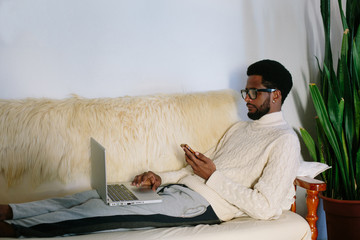 Portrait of young freelancer african man wearing glasses seating on sofa using laptop and mobile phone at home, confused expression face