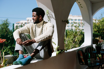 African man seating on balcony, enjoying summer sunny day outdoor at home