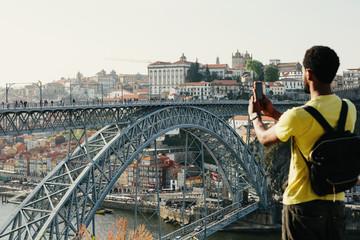 Traveler man doing photo on mobile phone. Porto, famous iron bridge and Douro rive on background