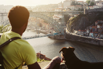 Traveler man with dog enjoying city view in Porto, famous iron bridge and Douro rive on background