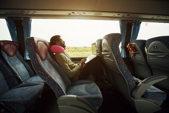 Portrait of smiling man using laptop computer in bus travel