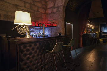 Modern jazz bar interior design, leather bar counter, lamp like music instrument design. Stone wall on background, brutal atmosphere
