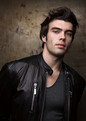 Young man in black leather jacket posing by metal walls. Portrait of the brunette in stylish clothes.