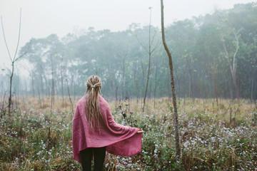 Blond woman wearing dread locks and pink blanket walking in fog field morning time
