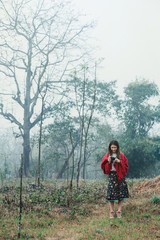 Young woman wearing red blanket doing pictures on compact camera and walking in fog field morning time