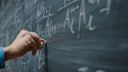 Close-up Shot of a Hand Holding Chalk and Writing Complex and Sophisticated Mathematical Formula/ Equation on the Blackboard.