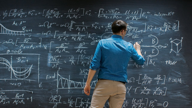Brilliant Young Mathematician Is Writing on Big Blackboard and Thinking about Solving Long and Complex Equation/ Formula.