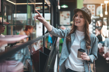 Smiling young woman is pointing at glass case while standing in cafe. She is wearing stylish hat and holding hot drink