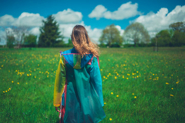 Woman wearing raincoat in meadow