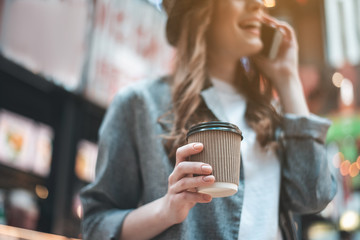 Low angle focus on woman hand holding cup of coffee. Cheerful girl is enjoying phone conversation