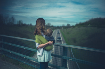 Young mother with baby on road bridge