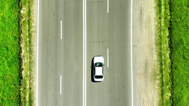 Aerial photo. A white car is driving along the highway parallel to the road markings. Concept of traveling by car.